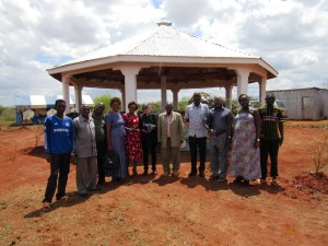 Members of the local committee standing with Rev Elder Pat Bumgardner and Rev Michael Kimindu (center) in front of the first Kimer-Kamba Cultural Centre building.