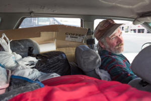 Many people in poverty in the USA live on the streets or in their cars like this man in his 1998 station wagon.